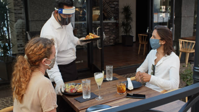 vídeos de stock e filmes b-roll de waiter wearing ppe during covid-19 pandemic bringing food to customers on patio - covid restaurant