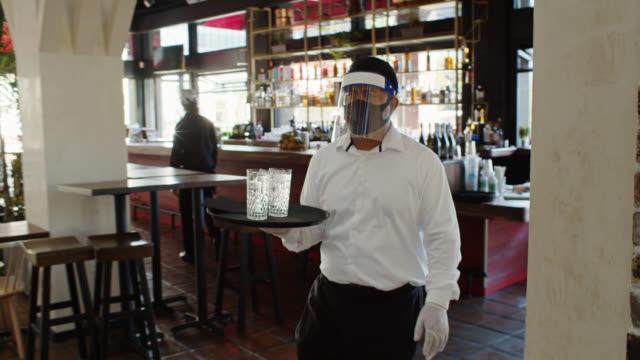 kellner trägt psa während covid-19 pandemie tragen tablett mit gläser wasser - bedienungspersonal stock-videos und b-roll-filmmaterial