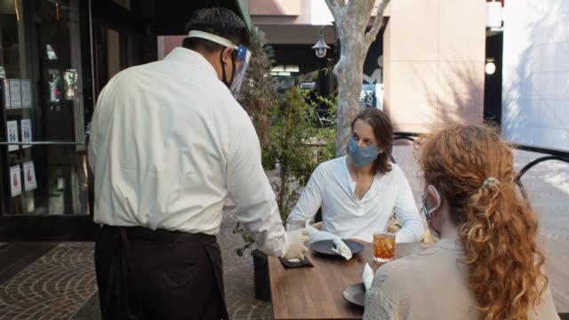stockvideo's en b-roll-footage met ober dragen ppe tijdens covid-19 pandemische serveert gemaskerde klanten op outdoor table - dineren
