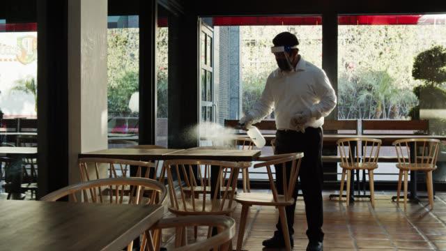 kellner trägt psa während covid-19 pandemie sprüh- und wischtische - bedienungspersonal stock-videos und b-roll-filmmaterial