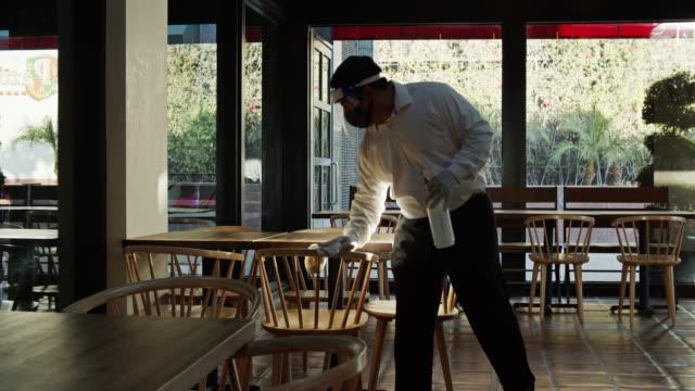 kellner trägt psa während covid-19 pandemie wiping down tische - bedienungspersonal stock-videos und b-roll-filmmaterial
