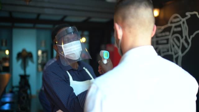 vídeos de stock e filmes b-roll de waiter wearing protective face mask and measuring temperature of customers - covid restaurant