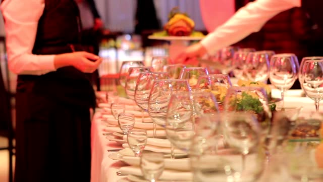 waiters are arranged wine glasses, banquet table in a restaurant, empty glasses on the banquet table, new year, christmas - matrimonio video stock e b–roll