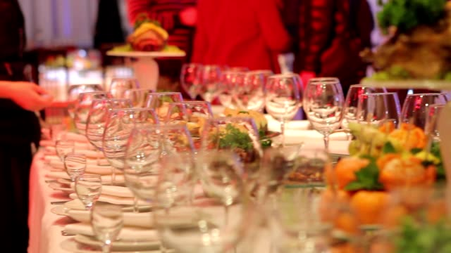 waiters are arranged wine glasses, banquet table in a restaurant, empty glasses on the banquet table, New Year, Christmas video