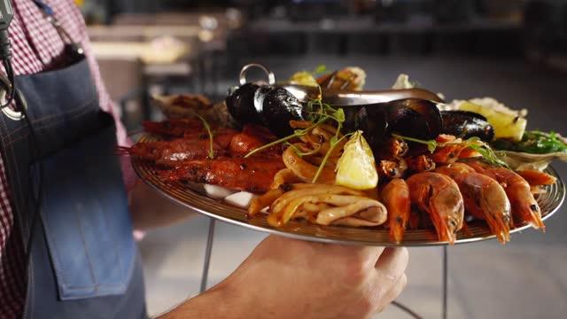 i camerieri trasportano piatti misti di pesce, gamberetti di aragosta, gamberoni, cozze, ostriche e calamari serviti su un grande piatto di salver per i visitatori del ristorante di lusso. garcon porta piatto tradizionale meditario - antipasto video stock e b–roll