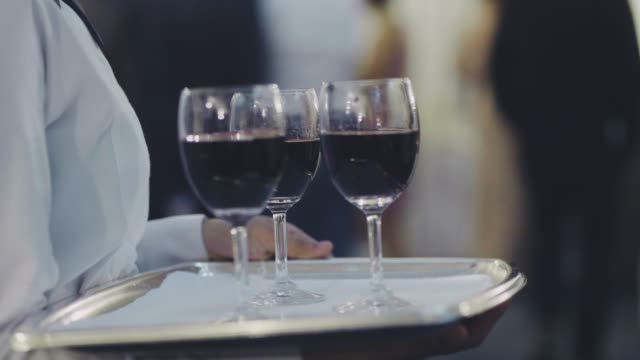 Waiters holds trays with glasses wine on reception Waiters with red wine flutes on trays tray stock videos & royalty-free footage