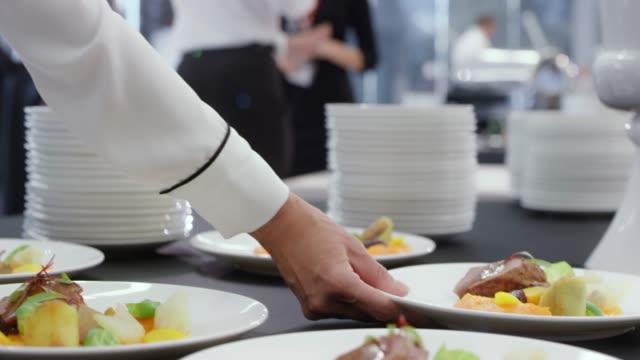stockvideo's en b-roll-footage met obers platen met het hoofdgerecht uit de tabel nemen - serviesgoed