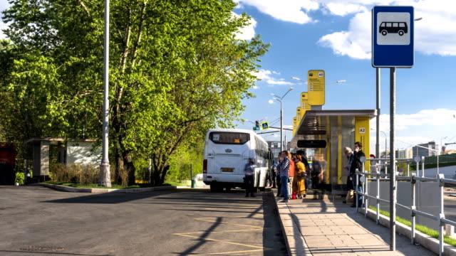 stockvideo's en b-roll-footage met wachten en aan boord van de bussen op de bus terminal, time-lapse - bushalte