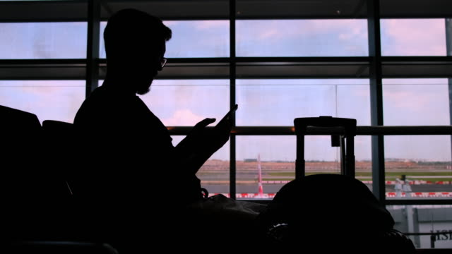 Waiting and killing time with phone when the flight is delayed Silhouette of man with cellphone in airport waiting area, view in the evening against the terminal windows. He has to wait till the night minority groups stock videos & royalty-free footage