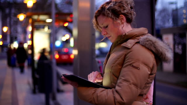 Waiting at Tram Platform Young woman with digital tablet pc at a Tram Platform.  bus stop stock videos & royalty-free footage