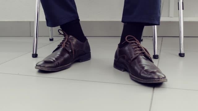 väntar. närbild av män skor. - sitta bildbanksvideor och videomaterial från bakom kulisserna