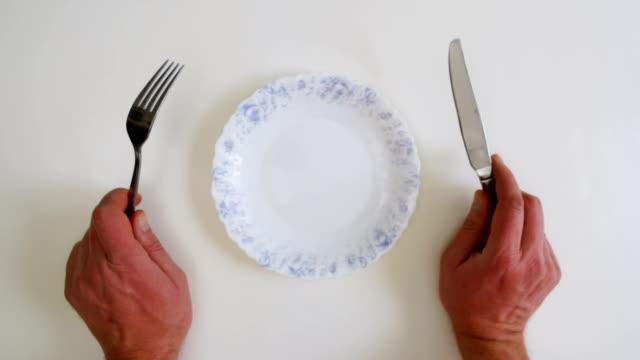 väntar på mat, håller en kniv i handen över en tallrik gaffel. - empty plate bildbanksvideor och videomaterial från bakom kulisserna