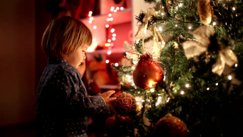 Waiting for Presents Under Christmas Tree Lovely little blond boy is standing by decorated Christmas tree and looking for gifts. christmas tree stock videos & royalty-free footage
