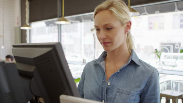 Waitress Adding Up Bill At Cash Register In Coffee Shop video