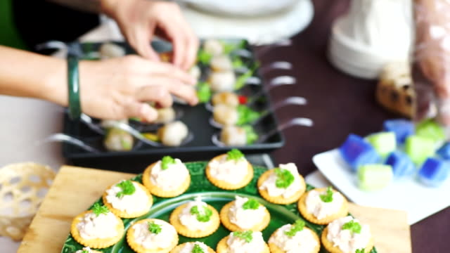 Waitress hand arranging pieces of canape in a plate on the buffet table.
