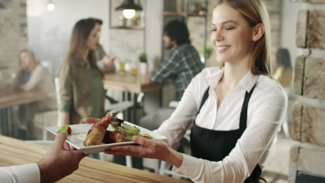 Waitress picking up food from the kitchen Waitress picking up food from the chef wait staff stock videos & royalty-free footage
