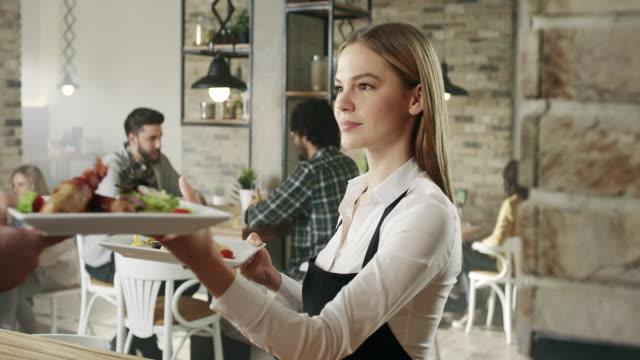 waitress picking up food from the kitchen - kelner filmów i materiałów b-roll
