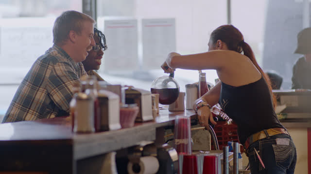 waitress pours coffee into coffee cups for young couple at an authentic diner counter - restaurang bildbanksvideor och videomaterial från bakom kulisserna