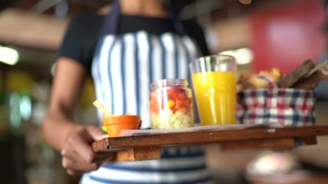 Waitress serving breakfast on a tray