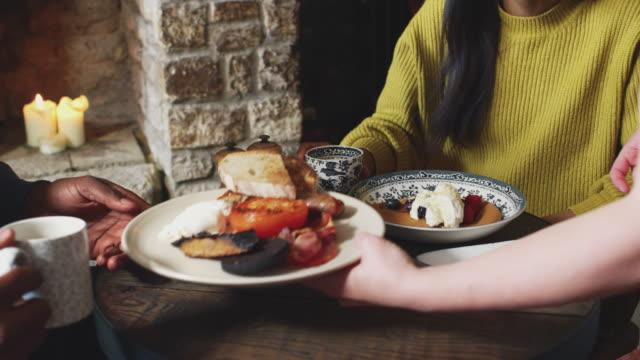 kellnerin serviert paar sitzen am tisch in traditionellen englischen ferienhotel gekochtfrühstück und pfannkuchen mit obst - küchenzubehör stock-videos und b-roll-filmmaterial