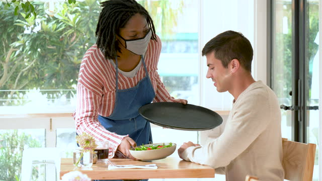 Waitress serving food to customer, wearing face mask