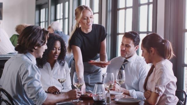 vídeos de stock, filmes e b-roll de refeição do serviço da empregada de mesa aos colegas do negócio que sentam em torno da tabela - almoço