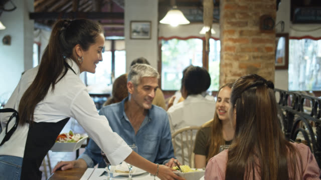 Waitress Serving Young Woman Dining Out with Parents in Argentinian Parrilla Restaurant video