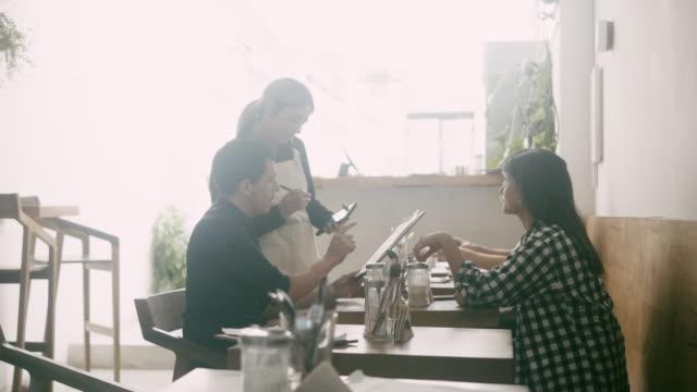 kellnerin nimmt bestellungen mit dem digitalen tablet entgegen - bedienungspersonal stock-videos und b-roll-filmmaterial