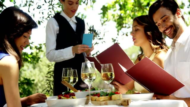 vídeos y material grabado en eventos de stock de camarera, teniendo una orden de parejas - gastronomía fina