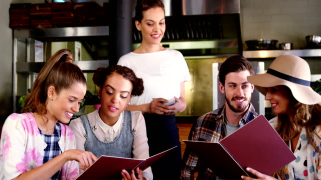 Waitress taking order from customers Waitress taking order from customers in restaurant menu stock videos & royalty-free footage
