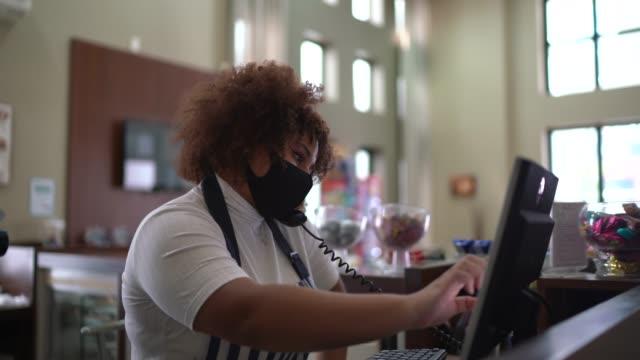 kellnerin spricht am telefon und registriert die bestellung des kunden in einem computer - mit gesichtsmaske - bucht stock-videos und b-roll-filmmaterial
