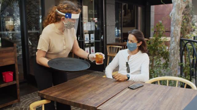 kellnerin trägt psa während covid-19 pandemie serviert getränk an maskierten kunden - bedienungspersonal stock-videos und b-roll-filmmaterial