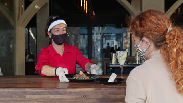 stockvideo's en b-roll-footage met serveerster die ppe draagt tijdens covid-19 pandemische portie gemaskerde klant door venster - dineren