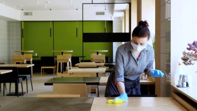 waitress, wearing protective gloves and mask, disinfects tables for visitors using antiseptic spray for protect coronavirus. reopening cafeteria or restaurant. safety concept