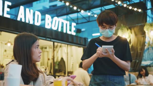 stockvideo's en b-roll-footage met de serveerster met een masker desinfecteert de lijst bij restaurant. - dineren