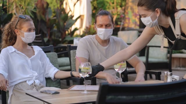 Waitress with protective medical mask and gloves serving guest with cocktails in outdoor restaurant.