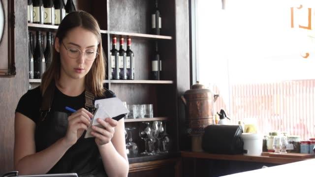 vídeos de stock e filmes b-roll de waitress working in cool bar taking orders - avental