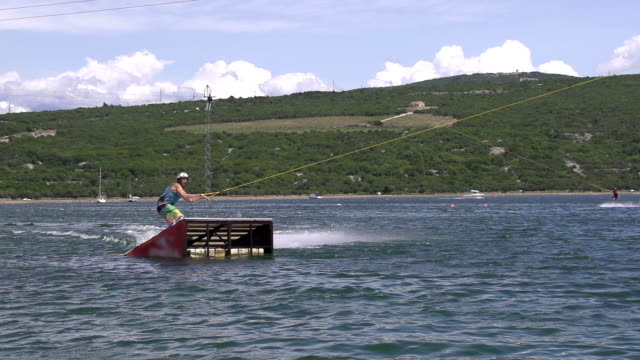 SLOW MOTION: wakeboarder jumps over the kicker video