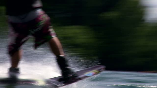 Wakeboarder on lake in slow motion Young man wakeboarding on lake in slow motion (HD, NTSC).     wasser videos stock videos & royalty-free footage
