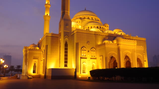 Walk along the Arabian mosque at night. A lone cyclist rides through the park alley. Illuminated gold lights mosque.