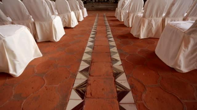 vidéos et rushes de marcher vers l'autel avec des sièges vides sur les deux côtés - baptême