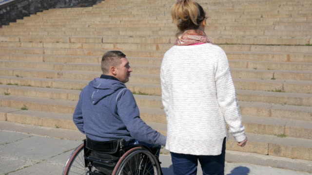Walk in park invalid on wheel chair and girlfriend, Couple lovers video