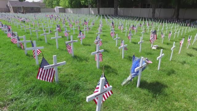 прогулка мимо военных крестов кладбища - memorial day стоковые видео и кадры b-roll