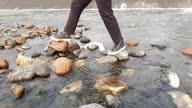 istock 4K walking across river stones 1309219027