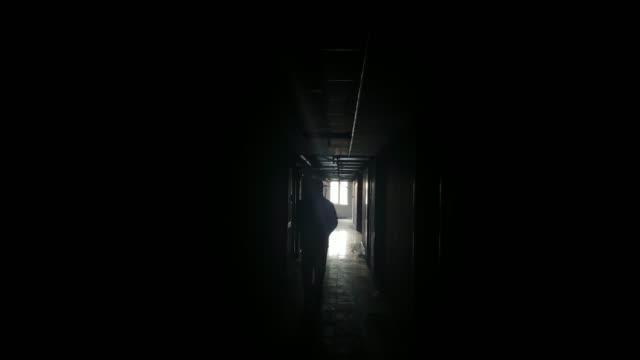 walking alone in the dark corridor - prigione video stock e b–roll