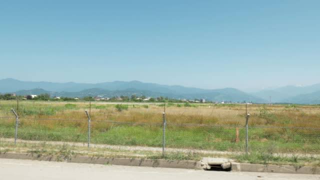 Walking along the barbed wire fence of the airport. Batumi, Geoargia video