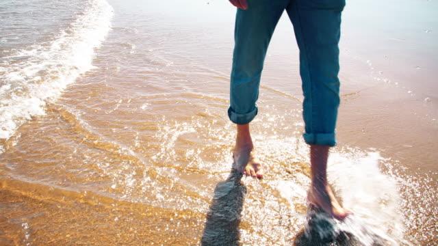 vandring längs sanden genom grunt havsvatten. - byxor bildbanksvideor och videomaterial från bakom kulisserna