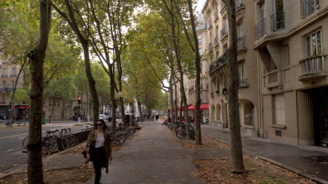 walking along the street with velib parking in paris, france - scendere video stock e b–roll