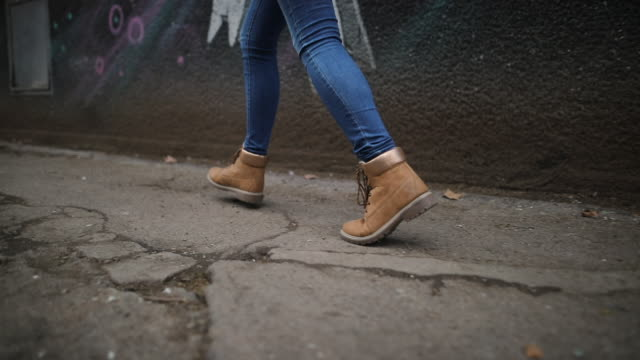 Walking and running in city in yellow boots Young women by the wall walking and running in city in yellow boots stepping stock videos & royalty-free footage