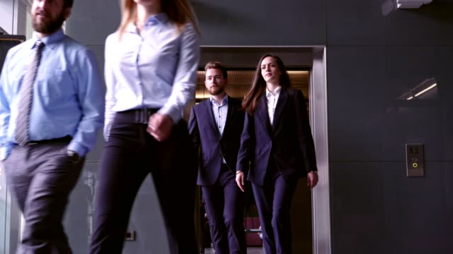 Walking and walking Business people walking out of the elevator. medium group of people stock videos & royalty-free footage